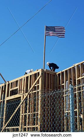 Picture of Two construction workers building new home, with wood ...