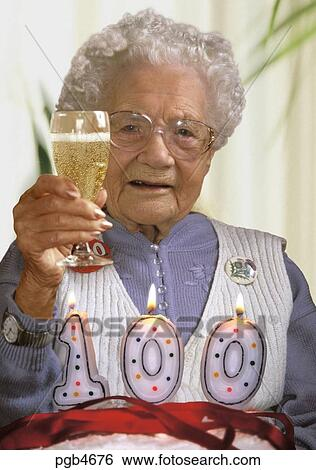 English Woman On Her 100th Birthday Toasting Family With A Glass Of Champagne Cake And Candles The Table In Front