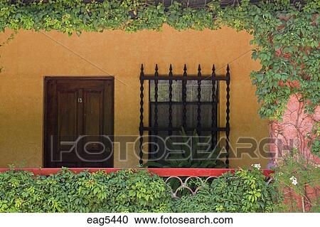 Stock Image   Wrought Iron Window Grate And Wooden Door Create The Mexican  Style Of This