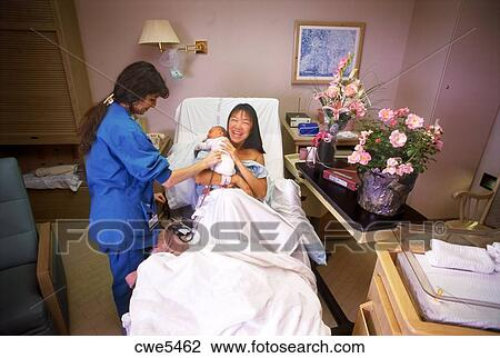 nurse tending to mother and newborn baby in hospital recovery room