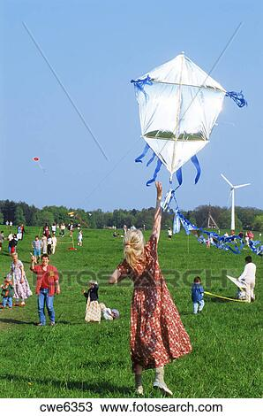 Stock Image - Families flying homemade kites together in Stockholm city park. Fotosearch