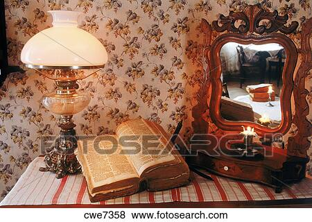 Antique wooden bureau with bible lamplight and mirror reflecting