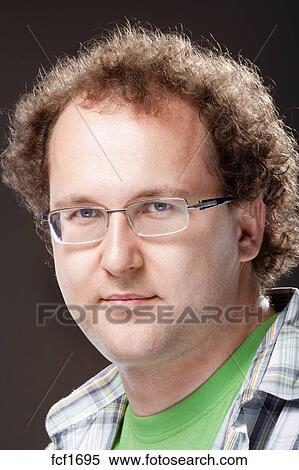 Ritratto, di, uno, giovane, con, capelli ricci, e, occhiali, , isolato, su, sfondo scuro Archivio fotografico