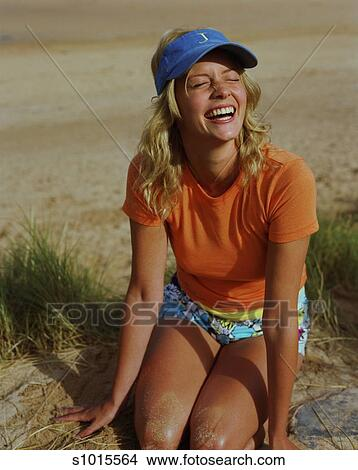 cba8a86d Stock Photo - Young woman wearing sun visor, kneeling on sand dune,  squinting.