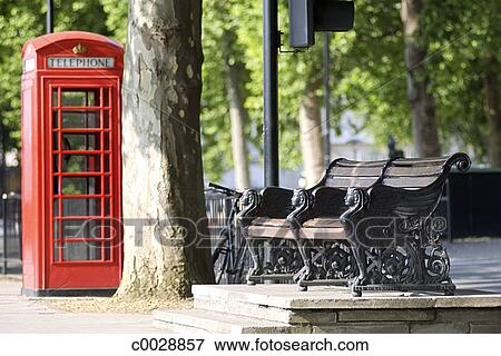Picture Of A Park Bench Near A Tree With A Red Telephone Booth In