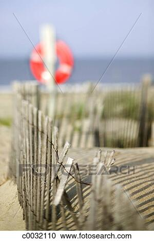 Selective Focus Of A Wooden Fence Leading To The Beach Where A Life Preserver Ring Hangs On A Post Stock Image