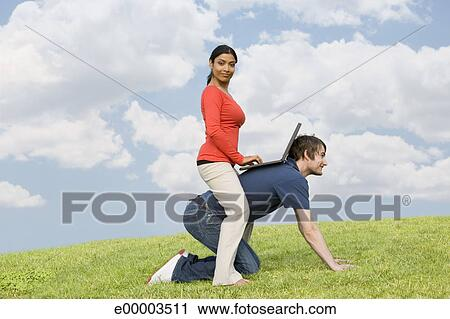 stock photography of woman riding man with laptop e00003511 search