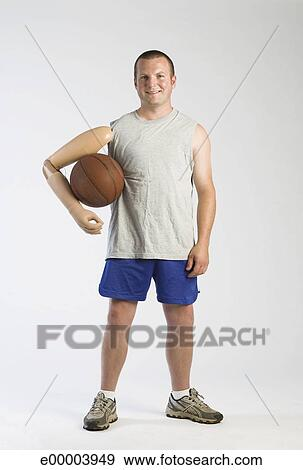 stock photograph of man with prosthetic arm holding basketball