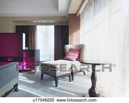 Awe Inspiring Chair And Ottoman In Bedroom Beside Window Stock Image Spiritservingveterans Wood Chair Design Ideas Spiritservingveteransorg
