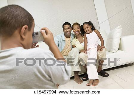 Boy Taking Picture of Family on sofa in living room Picture