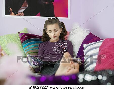 image pieds nue jeune fille lire magazine reposer lit beaucoup oreillers u18627227. Black Bedroom Furniture Sets. Home Design Ideas