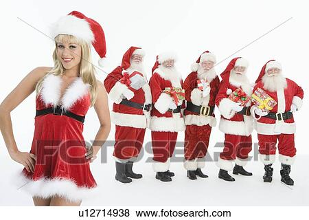 Group Of Men Dressed As Santa Claus Mrs Claus In Foreground