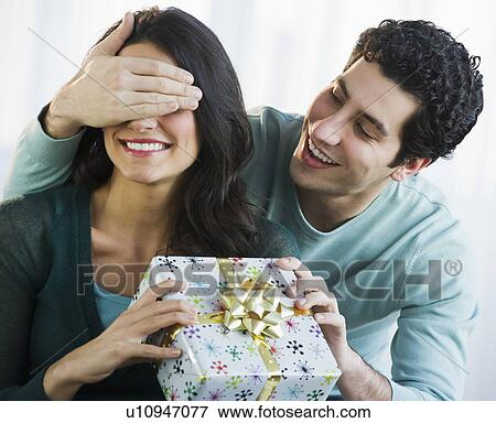 Picture Young Man Giving His Friend Present While Covering Her Eyes Fotosearch Search