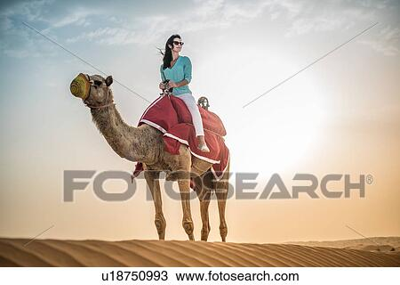 Stock photo of female tourist riding camel in desert dubai united female tourist riding camel in desert dubai united arab emirates altavistaventures Choice Image