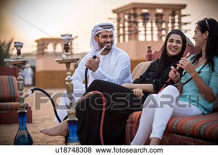 Local couple wearing traditional clothes smoking shisha on sofa with female  tourist, Dubai, United Arab Emirates Stock Photo