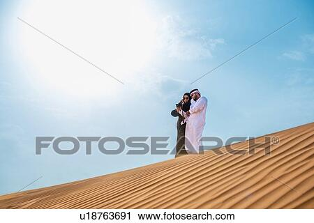 Middle eastern couple wearing traditional clothes taking smartphone selfie  on desert dune, Dubai, United Arab Emirates Stock Image