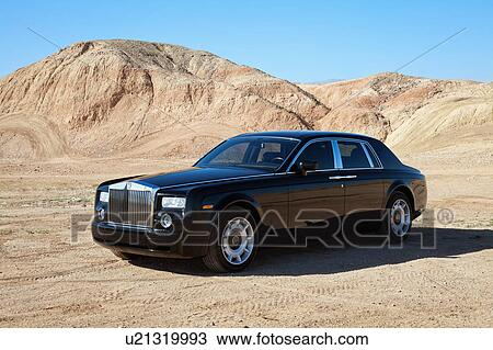 stock photo of rolls royce car parked on unpaved road in front of