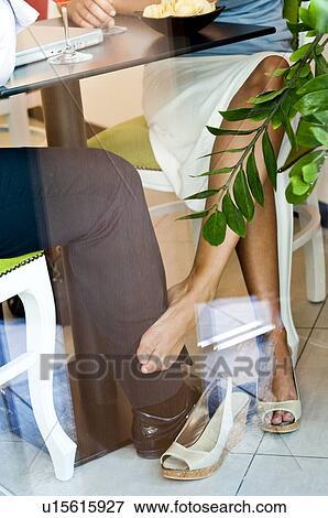 image jeune femme pied nu toucher jeune homme jambe sous table u15615927 recherchez. Black Bedroom Furniture Sets. Home Design Ideas
