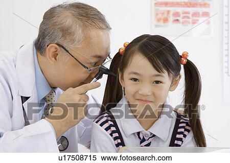 Doctor checking little girl's ear with medical equipment Stock Photography
