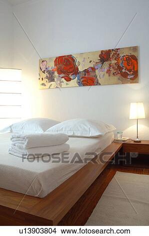 slaapkamer met schilderij boven de bed