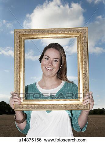 Stock Images of Young woman, holding frame up to face u14875156 ...
