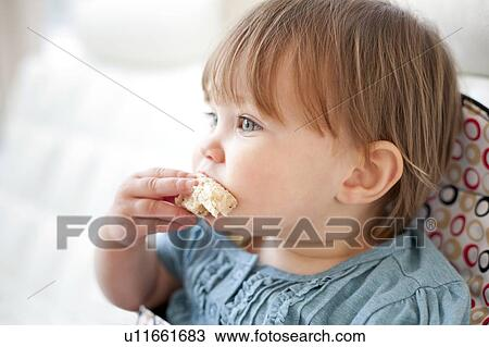 Toddler eating bread. She is 15 months old.