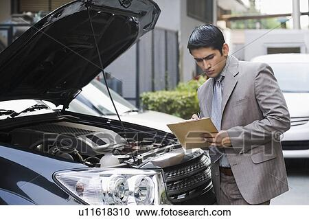 Insurance adjuster inspecting a car Stock Image ...