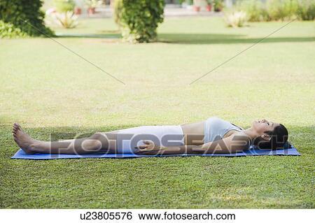 woman doing savasana corpse pose stock photograph
