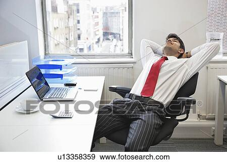 Stock Photograph Young Indian Businessman Relaxing In Chair At Office Desk Fotosearch Search