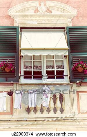 van flat venster met kant gordijnen groene houten kozijnen rode bloemen gebouw details frecoed op stucco hangend liguria itali