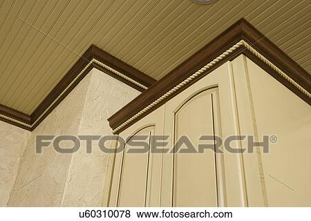Stock Photo Architectural Trim Dark Stained Crown Molding With Yellow Painted Cabinets Wainscot