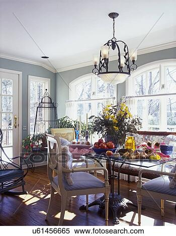 BREAKFAST AREA: Sunroom, pale sage painted walls with white trim, crown  molding, arched windows, cafe curtains, large floral on glass and iron  table, ...