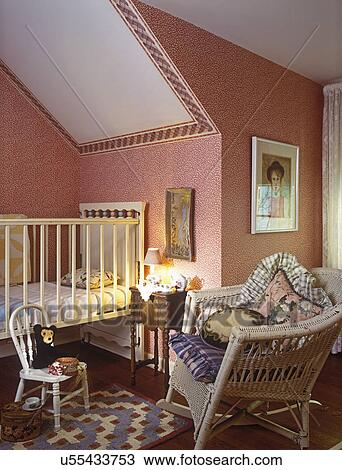 CHILDREN\'S BEDROOM: Crib on left. Pink wallpaper with border. Wicker chair  with cushions and pillows on right. Black stuffed bear near crib on tiny ...