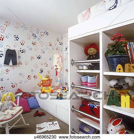 CHILDREN\'S BEDROOM: Storage area for toys and gear wear. Wallpaper and  bedding with hand and foot print design. Toys. Stock Image