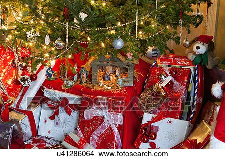 close up of gift boxes with decorated christmas tree