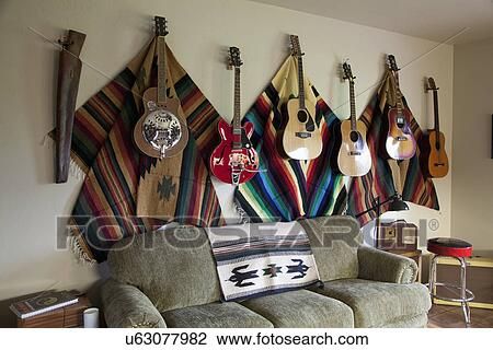 Collection of guitars hanging on wall in western themed living room;  Porterville; California; USA Stock Image