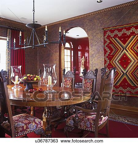 Stock Photo Of DINING ROOM   Sponge Painted Walls, Twisted Barley Looking  Crown Molding, Woven Red Rug Hangs On Wall, Iron Candle Chandelier, ...