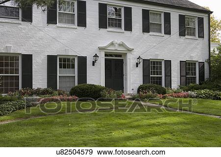 Exterior White Brick Traditional Colonial Home With Black Shutters Pediment Above The Door