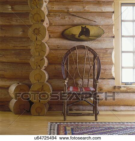 FURNITURE DETAILS: Rustic Twig Chair In Center With Tiny Red Cushion. Above  Tiny Semi Oval Painting Of Grizzly Bear.