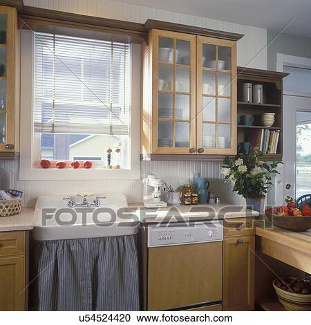 KITCHEN SINK DETAIL - Vintage sink with striped cotton sink skirt. Maple  stained cabinets with pebbled glass doors, blinds, wainscoting, molding  Stock ...