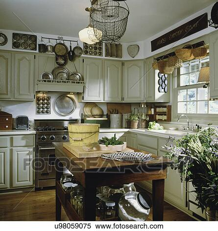 Kitchen with counter top, sink, cabinets, stove, island areas, herbs on  counter, pewter & tin cooking utensils on display, hanging light, and wood  ...