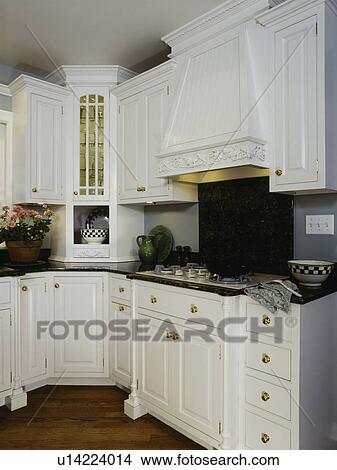 Kitchen With Customized White Wooden Cabinets And Range Hood