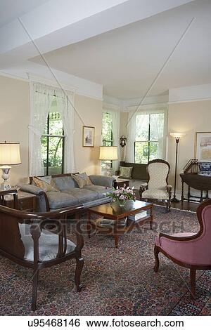 LIVING ROOMS: Restored Victorian, pale yellow walls, white trim work, lace  curtains, large oriental rug, antique Victorian furniture Stock Photograph