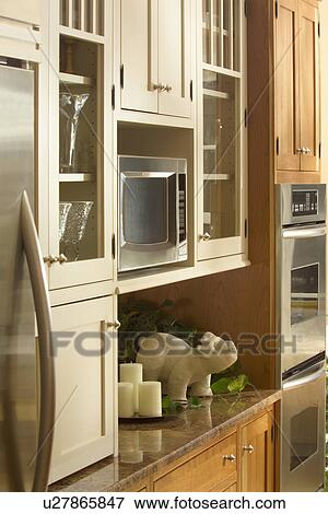 Microwave in wooden kitchen cabinet Stock Photo
