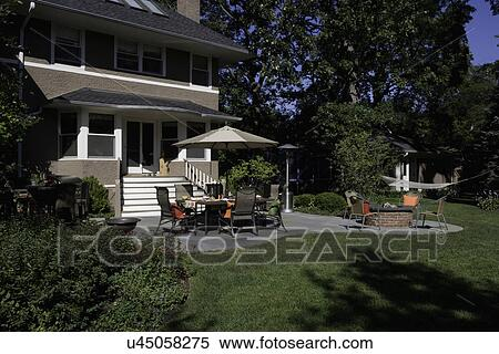 Patio Two Story Stucco Umbrella Over Dining Area Brick Fire Pit Hammock Stock Photography U45058275 Fotosearch