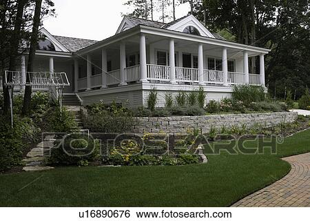 Porch Classical Wraparound Porch With Rows Of Columns On Cottage Cedar Shake Roof Stone Retaining Wall Border Gardens Arched Windows Brick Edging Separates Lawn Partial Brick Driveway Shows To Right Arbor With