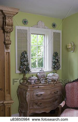WINDOW TREATMENTS: Corner of living room of a cottage style home, lime  green walls, French Provincial antique furniture and pottery, white  shutters ...