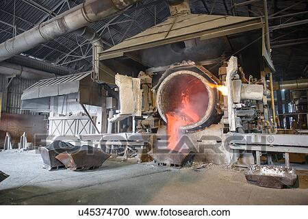Molten aluminum running into mold in recycling plant Stock Image