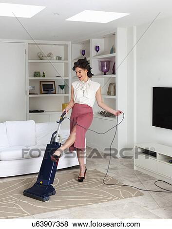 Pictures Of Young Woman Using Vacuum Cleaner In Living Room