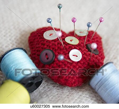 Heart-shaped pin cushion  buttons and thread Stock Photography